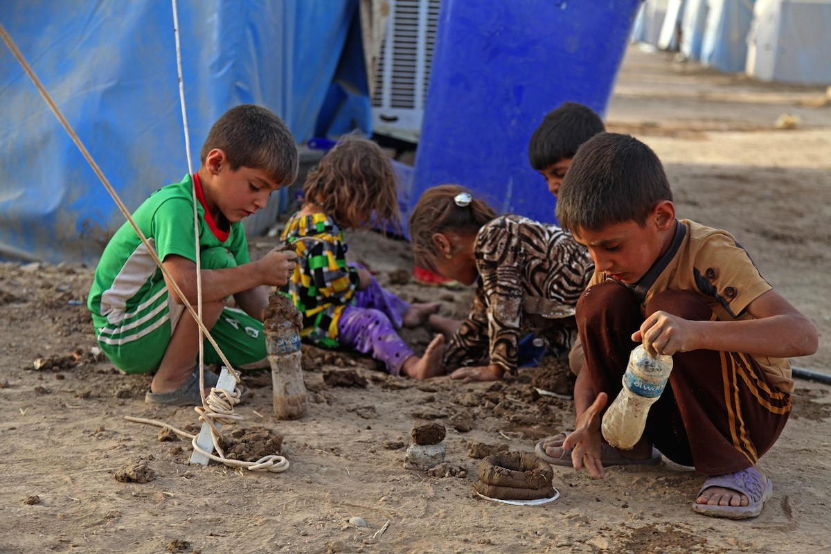 On 29 June 2014 in Iraq, children play in the dirt, outside a tent in the Khazar transit camp in the northern-eastern city of Erbil, capital of Kurdistan Region.