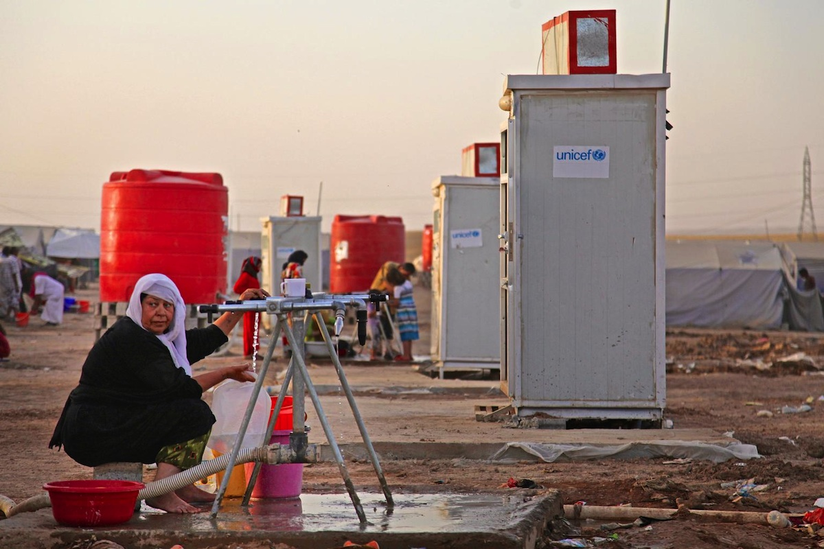 A displaced woman fills containers at a water point in the Khazar transit camp in the northern-eastern city of Erbil.