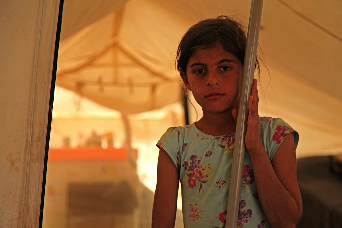 On 29 June 2014 in Iraq, 9-year-old Rasha Saleh, whose family has been displaced from the Kokjeli area in the conflict-affected city of Mosul, stands by a pole at the entrance to a tent in the Khazar transit camp in the northern-eastern city of Erbil.