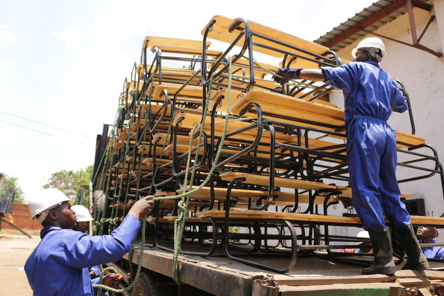 Workers in Malawi unload new, locally produced K.I.N.D. program school desks for UNICEF.