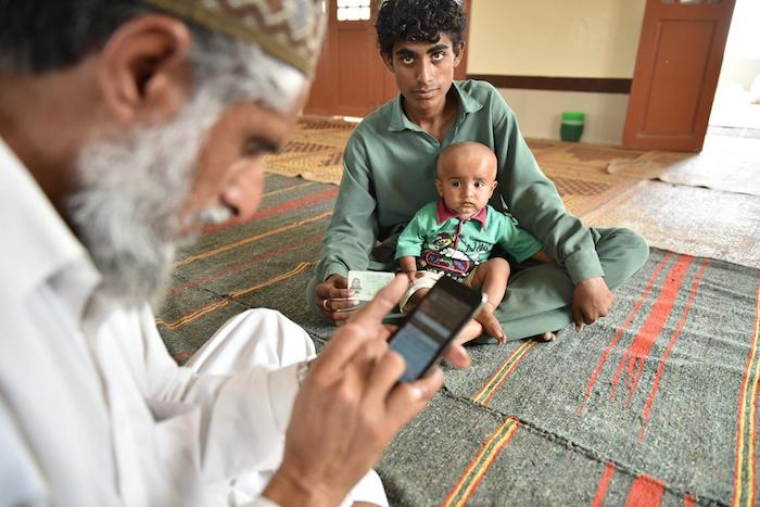 Father with his child at a mosque in Thatta district of Sindh province, Pakistan, where UNICEF and partners have launched a new digital birth registration service.
