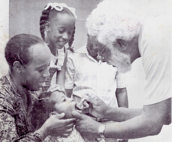Gail Hoad, in braids, looks on while her brother receives the oral polio vaccine during a national immunization campaign in Jamaica in 1982.