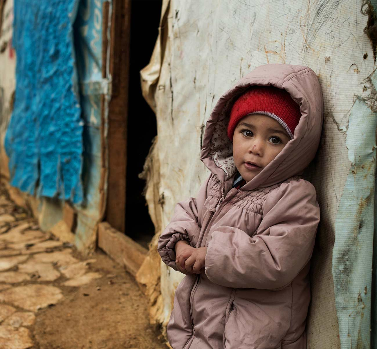 As with this young girl leaning against her ramshackle shelter UNICEF Provides winter coats and hats to thousands of children in Syrian Refugee camps - one of the countless ways UNICEF shelter and protects children around the world.