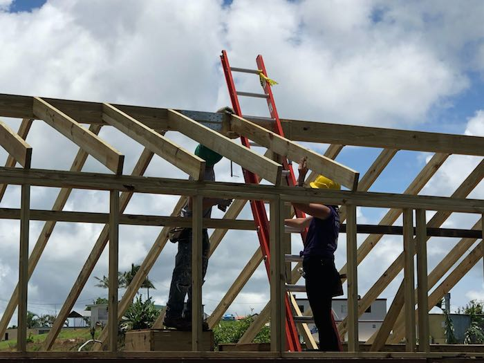 Student volunteers and skilled carpenters work together to repair roofs in Puerto Rico.