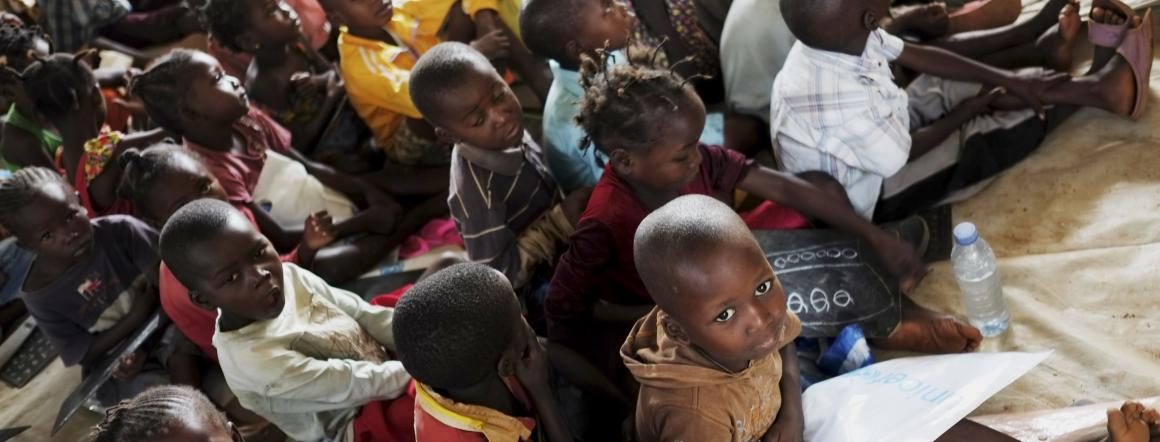 Children, seated on canvas covering the floor of a crowded classroom, attend a UNICEF-supported school in the Boy Rabe Monastery displacement camp in Bangui, the capital. © UNICEF/NYHQ2014-0326/Grarup;