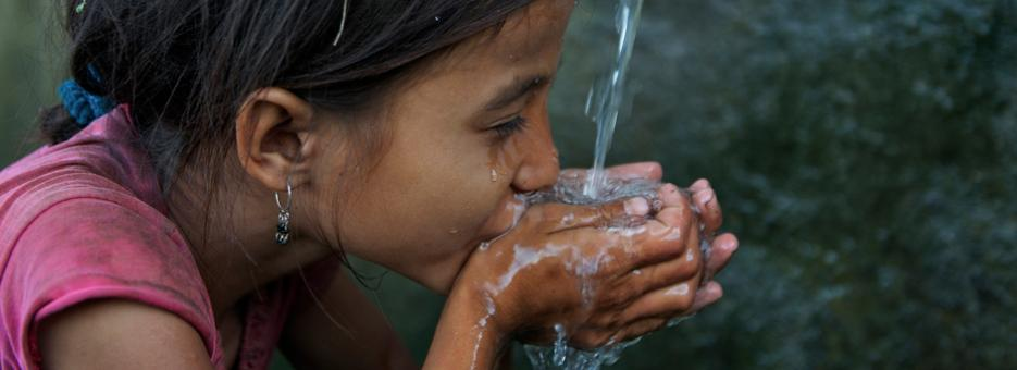 Saru Saud, 7, drinks water from her cupped hands, at a community water point in impoverished Biraltoli Village in Achham District in Far-Western Region in Nepal.