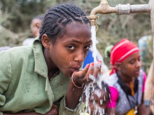 In Ethiopia, families had to walk through long stretches of bare fields under a hot sun to find water. Now that UNICEF has helped build a tap, children such as Mekdes Zewdu can drink water near home.