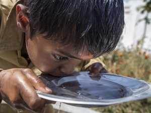 A young boy in Uttar Pradesh, India sips from a bowl of clean water as part of a UNICEF-sponsored, school-based project in 2011 to increase children's access to healthcare, safe water, good sanitation and proper hygiene.