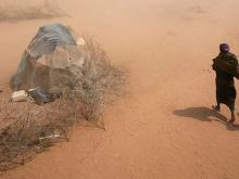 On 9 July, a woman and several children walk through a dust storm to their tent, in an area for new arrivals in the Dagahaley refugee camp in North Eastern Province, near the Kenya-Somalia border. The camp is among three that comprise the Dadaab camps, lo