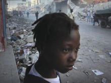 A girl stands in the aftermath of the Haiti earthquake in 2010