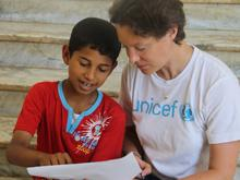 A young boy speaks with UNICEF Media Specialist Rebecca Fordham, at a UNICEF-supported workshop in the eastern city of Benghazi.