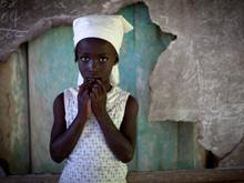 A girl stands in front of a broken chalkboard at a school in Pyechal, a mountainside village in the Department of Sud-Est.