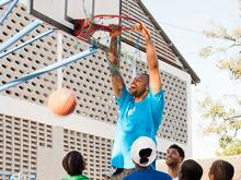 Paul Joynson Hicks dunks as children in Tanzania watch.