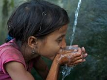Saru Saud, 7, drinks water from her cupped hands, at a community water point in impoverished Biraltoli Village in Achham District in Far-Western Region