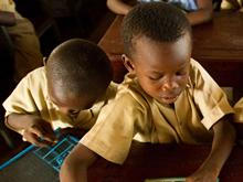 On 6 May, four boys work at a shared desk meant for two students, in an overcrowded classroom in Dixin Centre 2 Primary School in Conakry, the capital of Guinea.