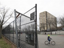 On 17 March 2020, a child rides a bike through an empty playground outside of Public School 24 in the Riverdale neighbourhood of the Bronx, New York City, United States of America.