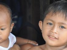 Gerald Alcaraz (right) sits in the doorway of the small family home in Tacloban, Philippines with his mother Richelle and his younger brother Jeffrey