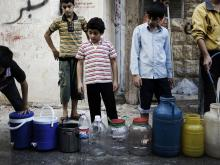 Syrian boys line up to fill jerrycans and other containers with water in Aleppo, Syria.