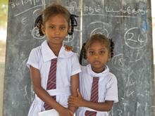Sisters T. Chandrakumari, 9, and T. Valarmath, 5, stand in front of a blackboard in a UNICEF-supported temporary learning space