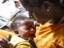 A mother holds her baby who is about to be vaccinated against tetanus
