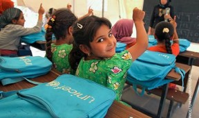 girls in classroom raising hands with blue UNICEF backpack: Inspired Gifts subhero