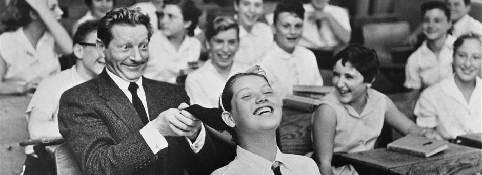 UNICEF Goodwill Ambassador Danny Kaye playfully pulls the hair of a girl seated in front of him, in a classroom filled with laughing children, during a visit to his primary-school alma mater, Public School 149 in the borough of Brooklyn in New York City.