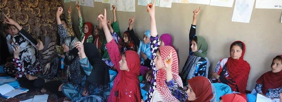 A group of young women raising their hands in a community-based school in Afghanistan
