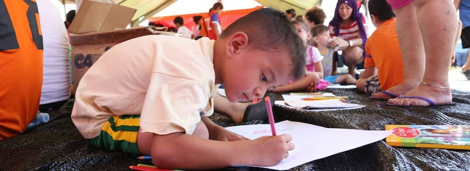 A boy draws in a UNICEF-supported, child-friendly space after the Ecuador earthquake
