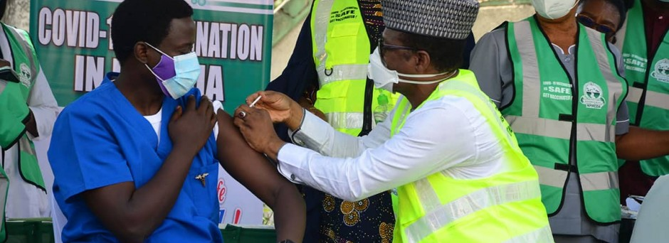 On 5 March 2021, in Abuja, Nigeria, Dr. Cyprian Ngong, in blue, is the first male health worker to vaccinated by Dr Faisal Shuaib Executive Director, NPHCDA. Dr. Ngong has been working in the isolation center at the hospital since March 2020.