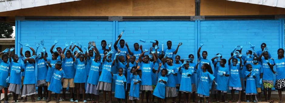 Children in blue UNICEF shirts smile and wave in front of a newly painted, newly constructed classroom built by bricks made of recycled plastic.