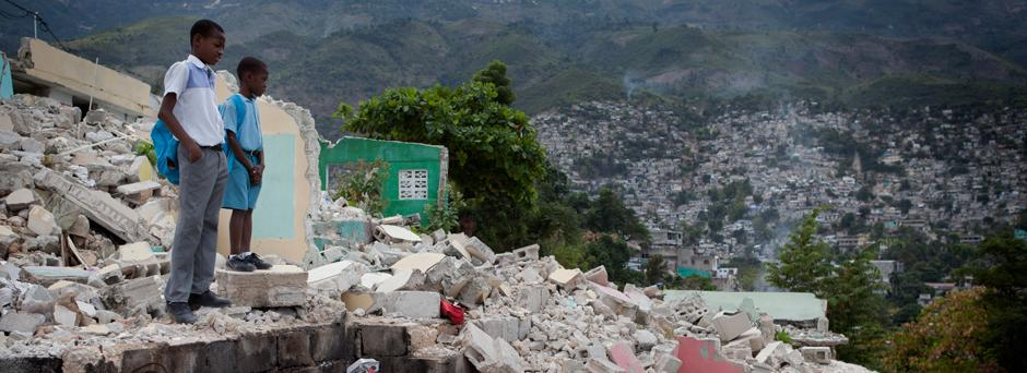 Standing among rubble and debris, students of St. Gerard School observe their school's construction site – as well as goats traversing the wreckage