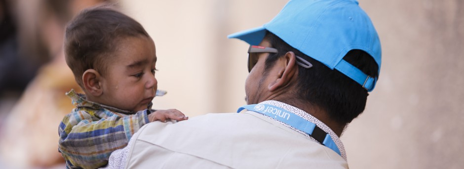 On March 20, 2018 in Adra in eastern Ghouta in the Syrian Arab Republic, a UNICEF Syria child protection specialist holds 6-months-old baby Yusuf as his mother queued for services.