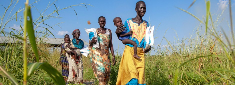 Women in Bienythiang, Akoka County, Upper Nile state, South Sudan carry UNICEF-supplied mosquito nets.