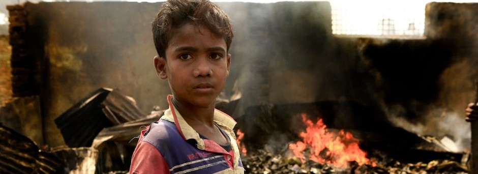 A 10-year-old boy stands amid damage caused by a fire that swept through Rohingya refugee camps in Cox's Bazar, Bangladesh, displacing thousands.