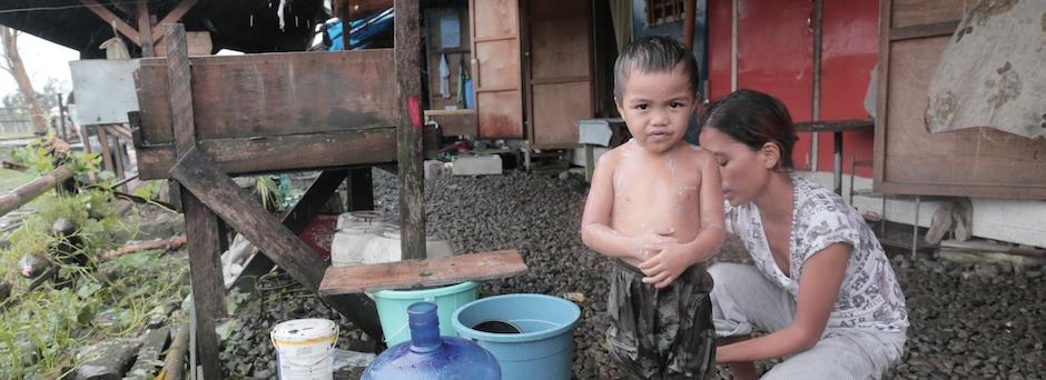 John Dave, 3, is getting bath at the Government Center bunkhouse in Tacloban City in Leyte Province, Eastern Visayas Region the day after Typhoon Hagupit made landfall.