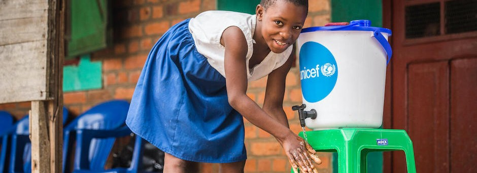 A student washes her hands outside Elikya Primary School in Mbandaka, DRC.