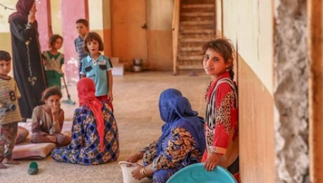 Women and children sit in the hallways of a school building being used as a shelter for displaced families in the village of Haji Ali in Ninewa governorate.