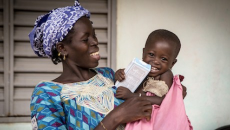 a 2-year-old girl from Mali holds a box of micronutrient powders which helps fortify her food and keep her healthy.
