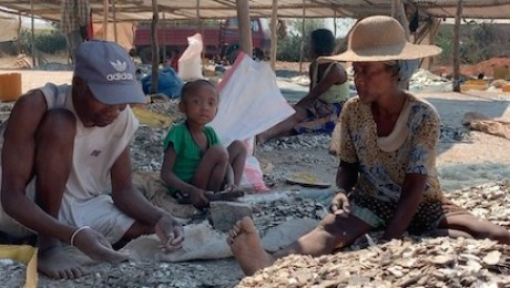 A man, woman and child sift through piles of rock for mica, the silvery mineral composite that ends up in everyday items like makeup and paint.