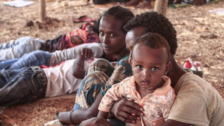 An Ethiopian refugee who fled fighting in Tigray province sits holding a child in a hut at the Um Raquba camp in Sudan's eastern Gedaref province, on November 16, 2020.