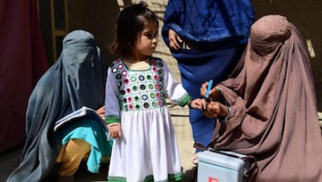 In Kandahar, Afghanistan, a UNICEF-supported polio vaccinator marks a girl's finger to indicate she has received the vaccine.