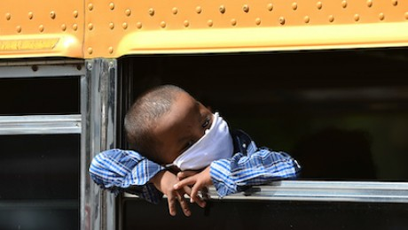 A boy take a bus from Tegucigalpa, capital of Honduras, back to his home community after his parents lose their jobs due to COVID-19.