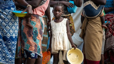 Children and families affected by Tropical Cyclone Eloise queue for food at an aid distribution point outside Beira, Mozambique.