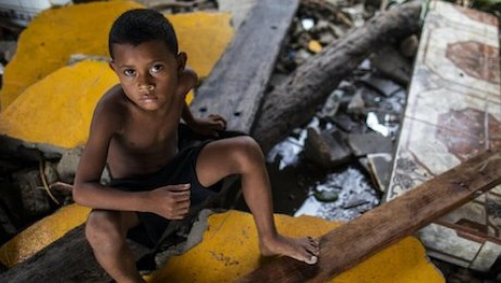 A boy in Bilwi, Nicaragua, sits on what remains of the family home in the wake of Hurricane Iota.