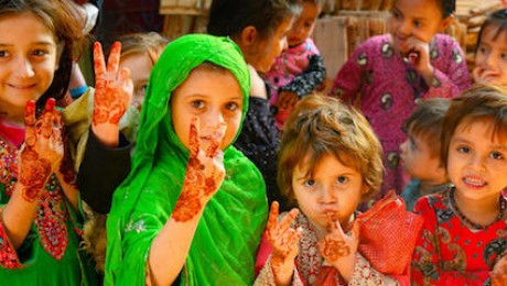 In Lahore, Pakistan, girls between the ages of 3 and 5 welcome a team of polio vaccinators in January 2021.