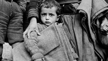 In the town of Castoria, Greece, circa 1950, a young refugee holds a folded UNICEF-supplied blanket in one hand and clutches his mother's skirt with the other.