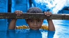 A young boy hangs on to a ledge outside his flooded home in the San Julian district, Santa Cruz Department, Bolivia. The flooding was caused by heavy rains related to climate change and the effects of La Niña.