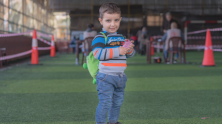 Syrian refugee child in Lebanon holds his mother's new LOUISE common card, which will allow the family to access all the cash-based aid programs for which they are eligible.