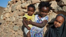 In February 2018, young girls stand outside their traditional stone home in the village of Assamo, Djibouti.