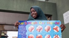 A young girl in Lagos, Nigeria holds a handwashing poster at a UNICEF-supported public awareness event to inform communities on how to protect themselves and their families from the novel coronavirus.